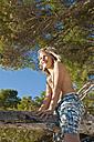 Spain, Mallorca, Boy sitting on tree at beach - MFPF000068
