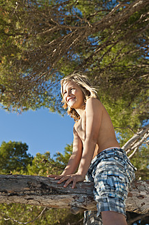 Spain, Mallorca, Boy sitting on tree at beach - MFPF000068