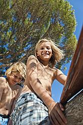 Spain, Mallorca, Children sitting on tree - MFPF000071