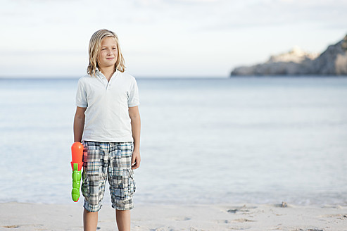 Spain, Mallorca, Boy with water gun on beach - MFPF000089