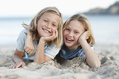 Spain, Mallorca, Children lying in sand on beach, smiling, portrait - MFPF000095