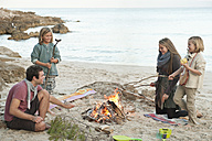 Spain, Mallorca, Friends grilling sausages at camp fire on beach - MFPF000107