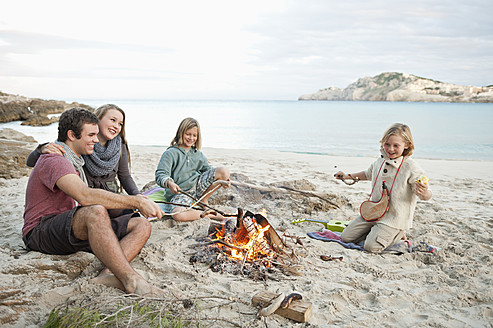 Spain, Mallorca, Friends grilling sausages at camp fire on beach - MFPF000113