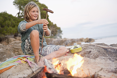 Spain, Mallorca, Boy barbecueing sausage on beach, smiling, portrait - MFPF000119