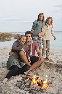 Spain, Mallorca, Friends at camp fire on beach - MFPF000122