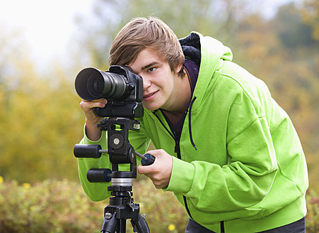 Austria, Young man taking photograph, smiling - WWF002137