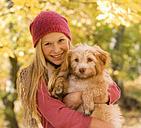 Austria, Teenage girl holding dog in autumn, smiling, portrait - WWF002162