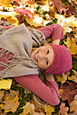 Austria, Teenage girl lying on autumn leaf, smiling, close up - WWF002165