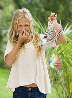 Austria, Teenage girl holding sneakers - WWF002258