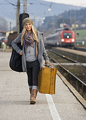 Austria, Teenage girl with suitcase on train station - WWF002263