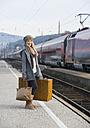 Austria, Teenage girl with suitcase on train station - WWF002266