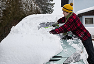 Austria, Young man cleaning snow on car - WWF002125