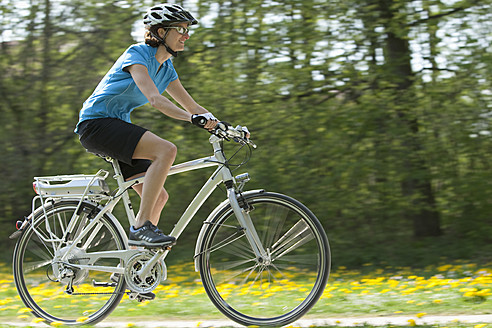 Germany, Bavaria, Munich, Mid adult woman riding electric bicycle - DSF000236