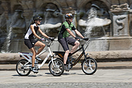 Germany, Bavaria, Munich, Man and woman riding electric bicycle - DSF000239