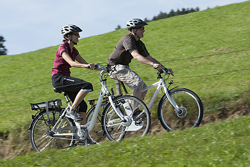 Germany, Bavaria, Man and woman riding electric bicycle - DSF000242