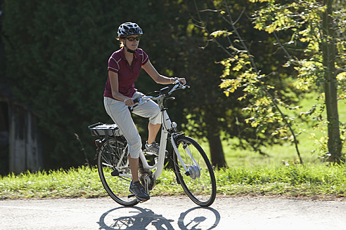 Germany, Bavaria, Mid adult woman riding electric bicycle - DSF000245