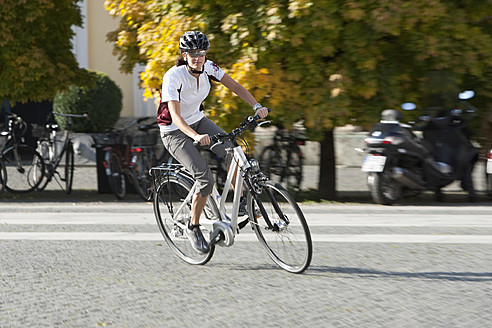 Germany, Bavaria, Munich, Mid adult woman riding electric bicycle - DSF000248