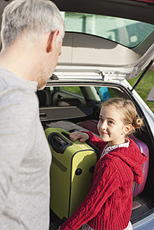 Germany, Leipzig, Father and daughter loading luggage into car - WESTF018425