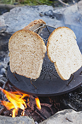 Europe, Belgium, Wholewheat bread toast on campfire - GWF001700