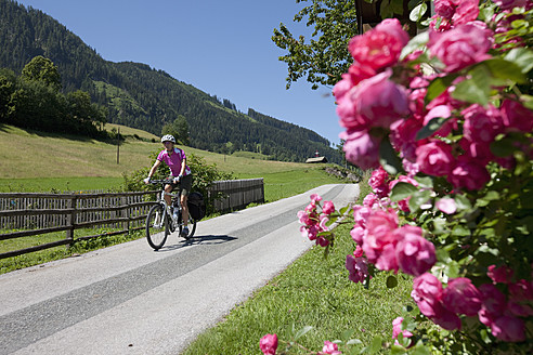 Austria, Salzburger Land, Mid adult woman riding bicycle - DSF000260