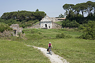 Italy, Mid adult woman riding bicycle - DSF000277