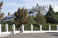 Spain, Andalusia, Vejer, Man and woman cycling through street - DSF000293