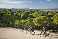 Spain, Andalusia, Man and woman riding bicycle on dirt track - DSF000290