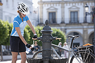 Spain, Andalusia, Woman filling water into bottle from drinking fountain - DSF000297