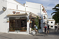 Spain, Andalusia, Conil de la Frontera, Man and woman cycling through street - DSF000285
