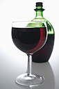 Red wine in glass and bottle on grey background - TCF002198