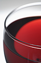 Glass of red wine against grey background - TCF002196