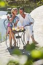 Austria, Salzburg County, Couple having breakfast on bridge over pond - HHF003952