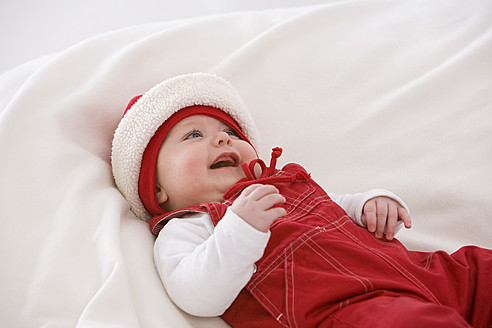 Baby girl lying on baby blanket, smiling - SMOF000509