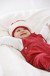 Baby girl lying on baby blanket, smiling - SMOF000510