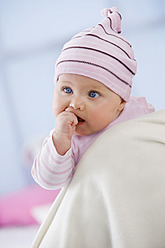 Baby girl in woolly hat with finger in mouth, close up - SMOF000513