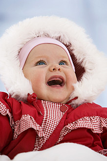 Baby girl in snow suit, smiling - SMOF000520