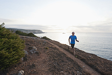 Portugal,Algarve,  Mature man jogging by coast - MIRF000365