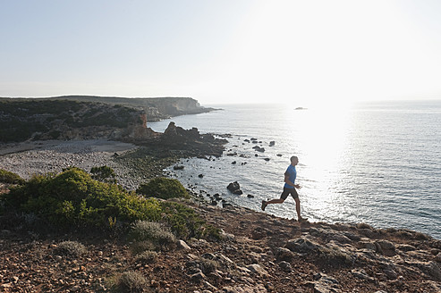 Portugal,Algarve,  Mature man jogging by coast - MIRF000368