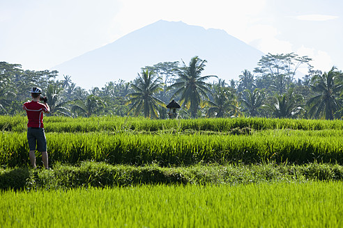 Indonesia, Bali, Man standing in field taking photograph, Mount Agung in background - DSF000213