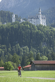 Germany, Bavaria, Mature man riding bicycle, Neuschwanstein Castle in background - DSF000225
