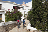 Spain,Ibiza, Puig de Missa,  Mature man and mid adult woman riding bicycle - DSF000305