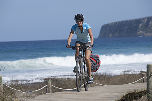 Spain, Formentera, Mid adult woman riding bicycle - DSF000384