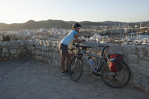 Spain, Ibiza, Eivissa, Mid adult woman with bicycle - DSF000320