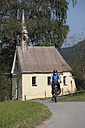 Germany, Bavaria, Man cycling through country road, chapel in background - DSF000332