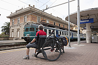 Italy, Liguria, Alassio, Mature man with bicycle at train station - DS000354