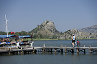 Turkey, Daylan Delta, Mid adult woman walking on jetty with bicycle - DSF000365