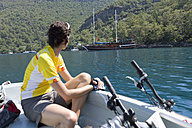 Turkey, Sarsala Bay, Mid adult woman with bicycle in boat - DSF000388