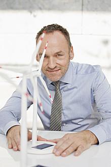 Germany, Leipzig, Businessman with wind power model - WESTF018509