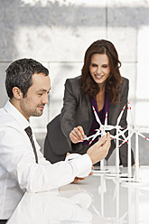 Germany, Leipzig, Business people discussing about wind power model - WESTF018533