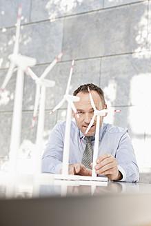 Germany, Leipzig, Businessman with wind power model - WESTF018539